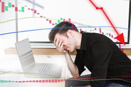 Man disappointed as stock price falls and money is lost. Stress and anger for day-trader. High risk.