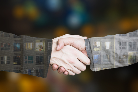 Teamwork begins with business agreement with blurred city background.