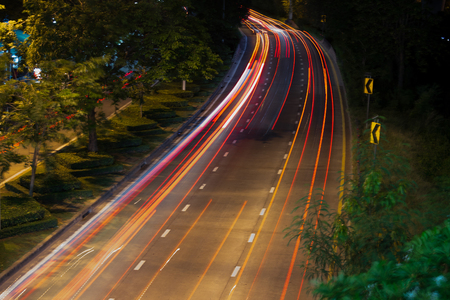 Bend in the road with long exposure and highway that curves to the right.  Cars coming in both directions at night, illuminating the roadway with street lights. Stock Photo