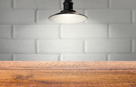 Old studio professional lighting template for product display.  Aged wooden table and faded old brick.  Classic hanging light.