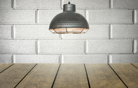 Rustic old studio with wooden table for product display or showcase and bright light shining from the top.  Brick wall blurred background. Stock Photo