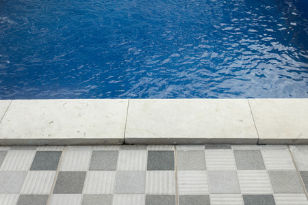 Luxury pool setting with wooden deck and well designed pool layout for relaxation. Stock Photo