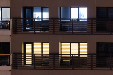 Apartment windows at night in the city. Stok Fotoğraf