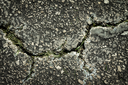Flaws and defects give to weakness shown by cracked pavement.  Imperfections and rough asphalt. Stock Photo
