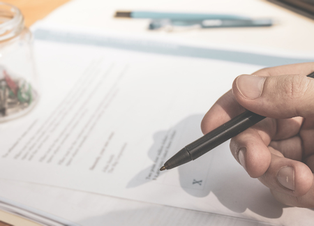 Hand signing papers for formal business signature.  Finance and monetary agreement.