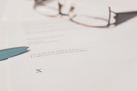 Hand signing legal contract for gaining ownership of company.  Binding legal contract. Stock Photo