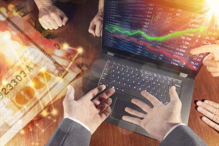 Stock market investment concept gain and profits with candlestick charts and numbers while financial business team debates and meets to discuss. Stock Photo
