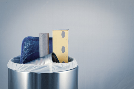 Isolated trash bin garbage container with refuse and recycling waste inside.  Environmental cleanup and waste concept. Stock Photo