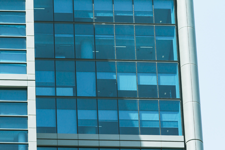 Building facade with modern window design for steel glass office tower.  Copy space and fade.