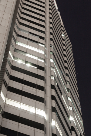 Corporate business building facade at night with lighted windows. Фото со стока