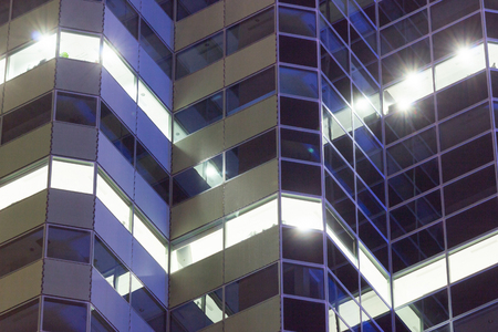 Corporate business building facade at night with lighted windows. Stock fotó