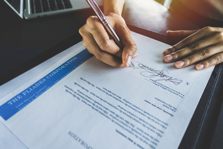 Financial business contract. Reading paperwork details and signing business contract.