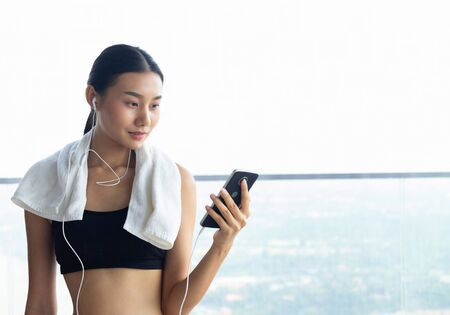 Fitness center workout and gym routine application on mobile device.  Young healthy and pretty girl using her phone in the gym while working out.