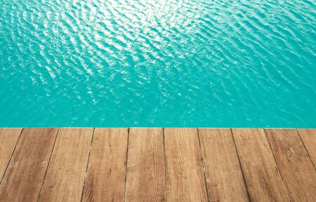 Pool with wood open copyspace area.  Beautiful clean swimming pool with bright blue water.  Luxury relaxation and lifestyle travel concept.
