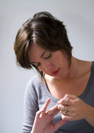 A portrait of an attractive young adult woman looking at her fingers on a white background.