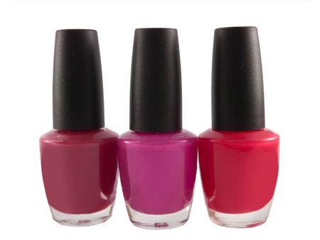 A close up on three bottles of red fingernail polish isolated on a white background.