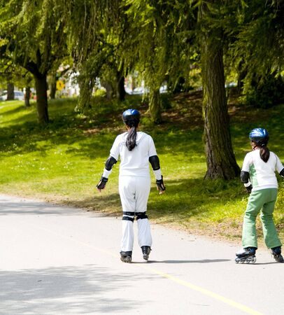 rollerblade: A mother teaching her daughter to rollerblade. Stock Photo