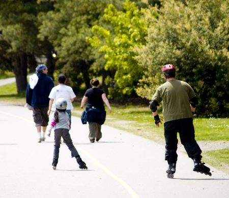 rollerblade: A father teaching his daughter to rollerblade.
