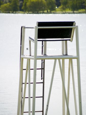 oversee: A life guard chair next to a lake.