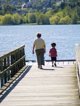 A grandmother walking with her grandson on the pier.