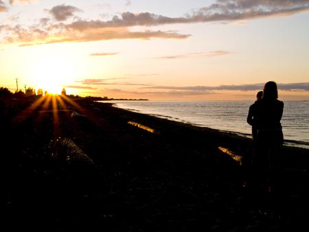 strait of juan de fuca: Two girls chatting on the beach under a golden sunset over the Strait of Juan de Fuca in Sequim, Washington.