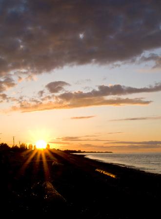 strait of juan de fuca: A golden sunset over the Strait of Juan de Fuca in Sequim, Washington. Stock Photo