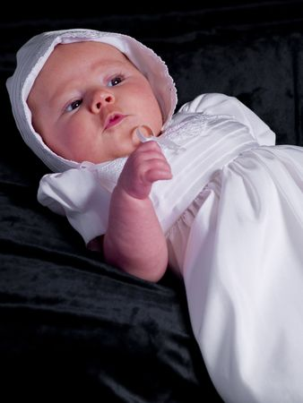 A portrait of a baby girl in a christening dress on a dark background. This photo has a shallow depth of field and the focus is on her right eye. Imagens