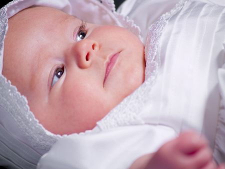 A portrait of a baby girl in a christening dress on a dark background. This photo has a shallow depth of field and the focus is on her face.