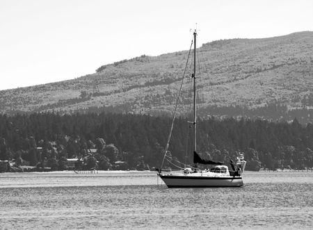 strait of juan de fuca: A sailboat off the shore of the Strait of Juan de Fuca in the Pacifc Northwest.