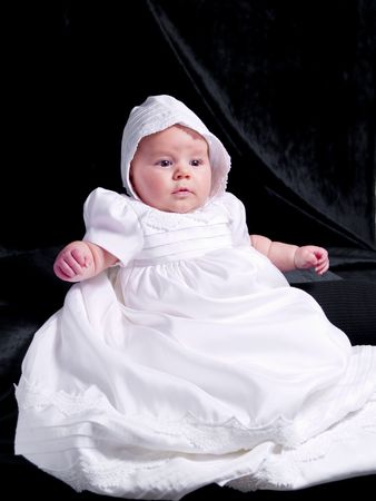 A portrait of a baby girl in a christening dress. Imagens