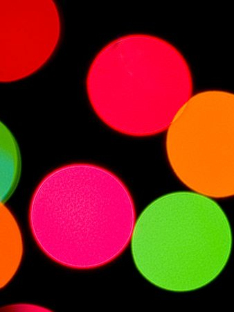 intentionally: Colorful lights on a dark background. Lights are intentionally out of focus for a blurred effect. Stock Photo