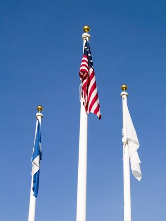 flagpoles: Three flags on poles on a calm day with a bright blue sky behind them.  Stock Photo