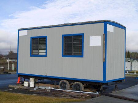 따뜻한 화창한 날에 건설 현장에서 바퀴에 작은 휴대용 사무실.