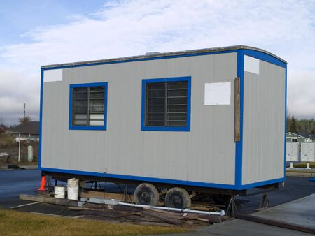 A small portable office on wheels at a construction site on a warm sunny day.