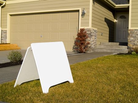 A close up on a blank sign in front of a house.