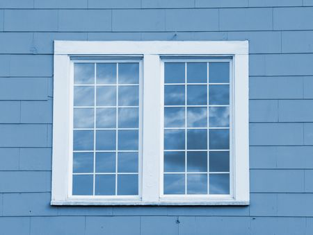 A close up on a single window with clouds reflected in the glass.
