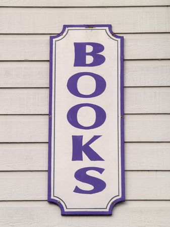 A close up on a sign with the word BOOKS on it.