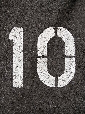 integer: A close up on white stenciled number ten on black pavement.