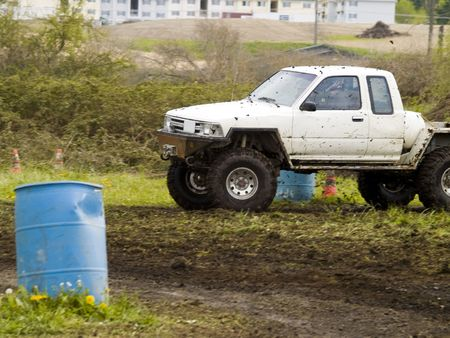 A truck racing through the mud in an off road competition. Slight motion blur.