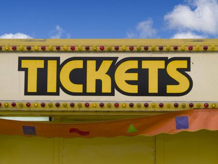 A close up on a sign at a fair that has the word TICKETS on it.