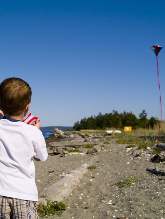 A young boy flying a kite at the beach on a sunny summer day in the Pacific Northwest. photo