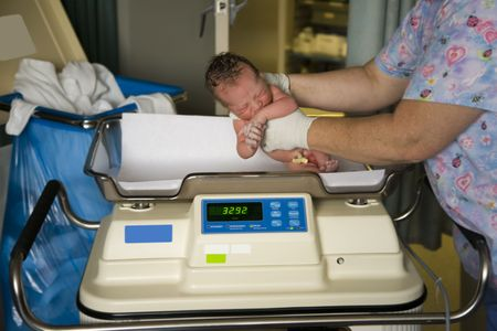 A newborn baby boy in the hospital just minutes after her was born about to be weighed. Very shallow DOF Stock Photo - 3574792