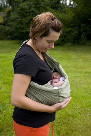 A portrait of a mother holding her newborn baby outside in a sling.  Stock Photo