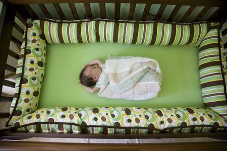 A week old baby in a crib. Shallow DOF photo