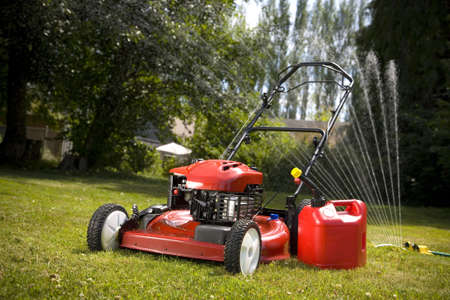 cut grass: A red lawn mower and gas can in fresh cut grass. Stock Photo