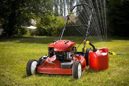 Een rode gazon mower en gas kunnen in verse cut gras.