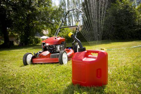 Een rode grasmaaier en gas kan in vers gesneden gras.