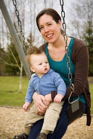 A young mother and her son on a swing in a park having fun. photo