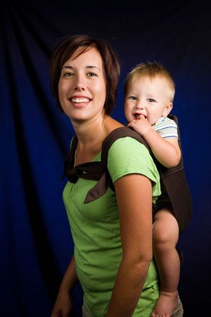 A young mother holding her one year old son in a baby carrier. photo