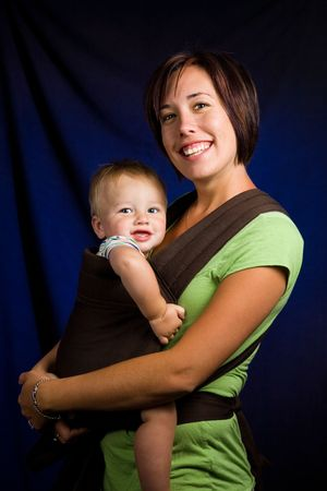 A young mother holding her one year old son in a baby carrier.